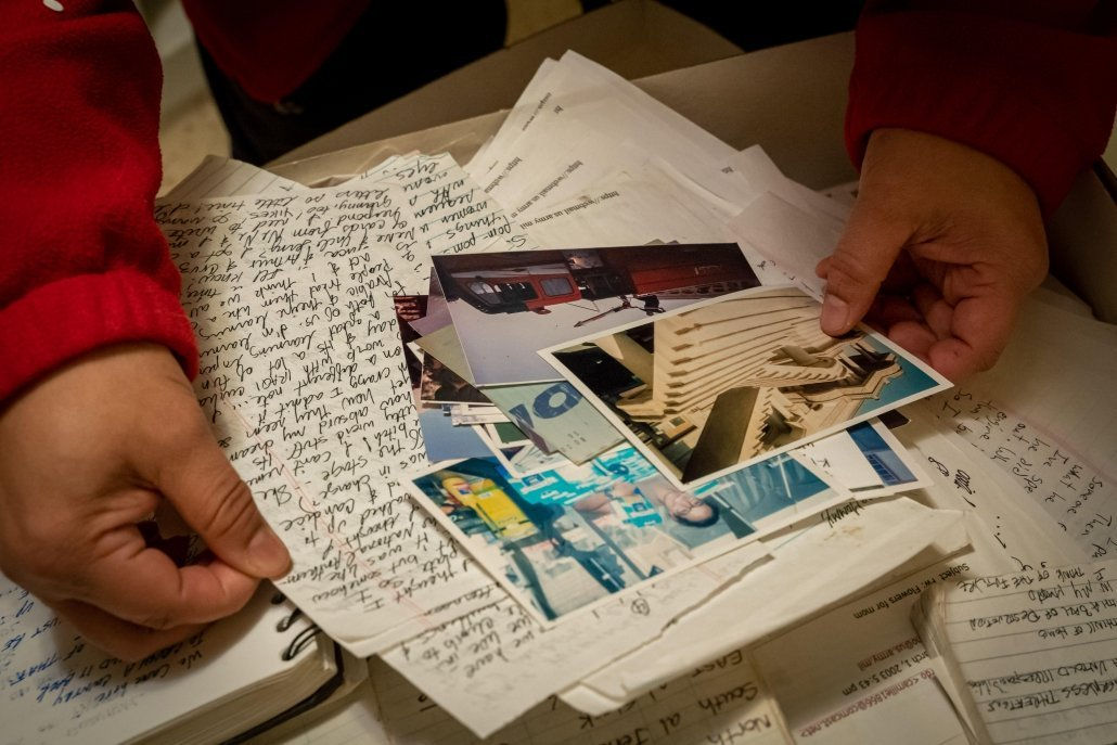 Yvette Pino shuffles through her saved letters, notebooks, and photos from Iraq. Photo courtesy Denita Long