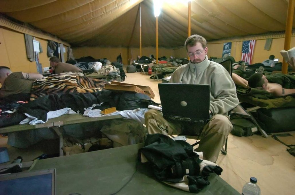 Jeremy Redmon writing on assignment for the Richmond Times-Dispatch in Kuwait in 2005. He embedded with U.S. troops during three trips to Iraq between 2004-2006. Photo courtesy of Dean Hoffmeyer, Richmond Times-Dispatch.