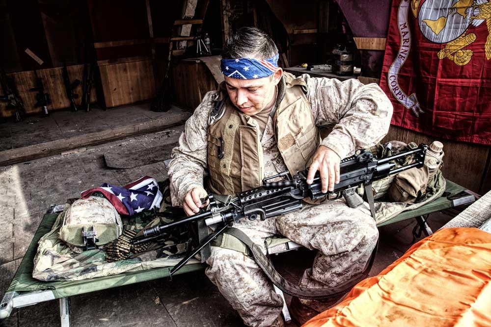 Marine Corps machine gunner, wearing confederate flag bandana, checking gun barrel