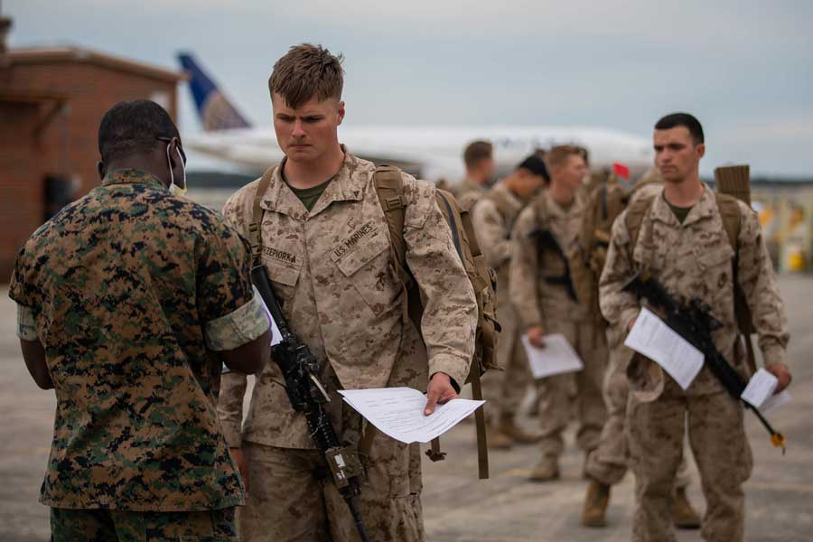 Marines returning from deployment answer screening questions as a part of a prescreening for the coronavirus on Marine Corps Air Station Cherry Point, North Carolina, March 30, 2020. Credit: Lance Cpl. Scott Jenkins/Marine Corps