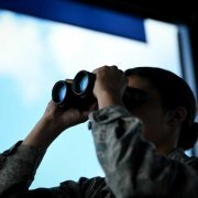 An air traffic controller uses binoculars to look for birds or other hazards that can damage aircraft. Photo credit: Airman 1st Class Nathaniel Hudson