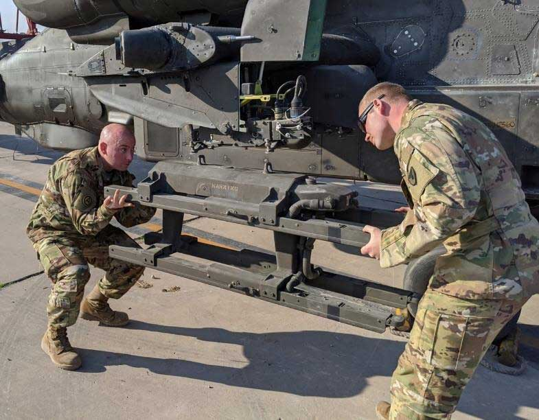 Staff Sgt. Brandon Prall and Sgt. Christopher Adams, 1107th Aviation Group, install hellfire missile racks on an AH-64E Apache Helicopter at Camp Taji, Iraq, in January. Photo by CW3 Grant Hutcheson, courtesy of the U.S. Army National Guard.