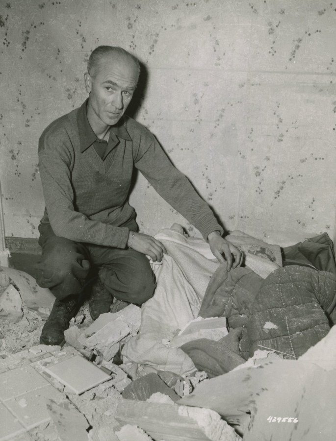 Ernie Pyle looking at his bed from which he had just left to watch the bombing, when the roof fell on it. Nettuno Area, Italy March 16, 1944