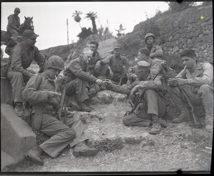 Ernie Pyle rests on the roadside with a Marine patrol April 8, 1945