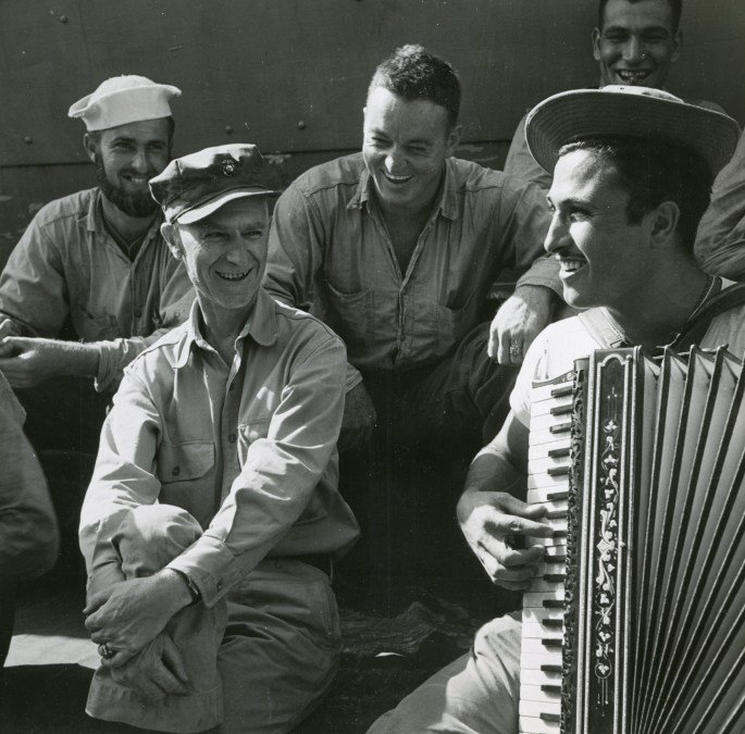 Ernie Pyle with troops listing to PFC Johnny Maturello play accordion aboard USS Charles Carroll (APA-28) while enroute to Okinawa March 1945
