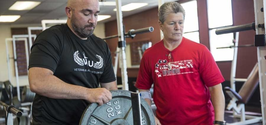 U.S. Marine Corps veteran Charles Dane adds weight to the bar during a 2018 Defense Department Warrior Games powerlifting practice at Cheyenne Mountain High School in Colorado Springs, Colorado. Dane was medically retired from the military after a 19-year career. Photo by Cpl. Juan Madrigal, courtesy of the U.S. Marine Corps.