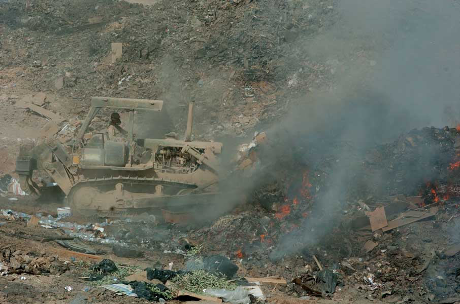 Sgt. Richard Ganske, 84th Combat Engineer Battalion, uses a bulldozer to maneuver refuse into the burn pit, sorting and burning it to manage sanitation requirements in 2004 at Joint Air Base Balad (formerly Logistics Support Area Anaconda) in Iraq. Photo courtesy of U.S. Army.