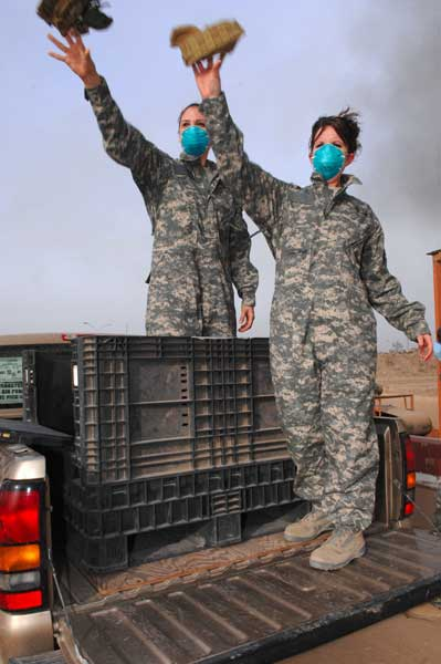 Senior Airman Frances Gavalis and Staff Sgt. Candice Zalewski, 332nd Expeditionary Logistics Readiness Squadron equipment managers, toss unserviceable uniform items into a burn pit at Joint Base Balad, Iraq, in 2008. Photo by Senior Airman Julianne Showalter, courtesy U.S. Air Force.