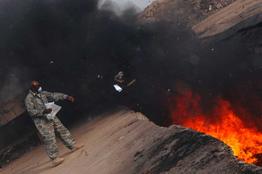 Master Sgt. Darryl Sterling, 332nd Expeditionary Logistics Readiness Squadron equipment manager, throws trash into a burn pit at Joint Base Balad, Iraq, in 2008. Photo by Senior Airman Julianne Showalter, courtesy U.S. Air Force.