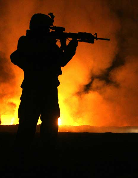 Sgt. Robert B. Brown from Fayetteville, N.C., with Regimental Combat Team 6, Combat Camera Unit watches over the civilian firefighters at the burn pit as smoke and flames rise into the night sky behind him at Camp Fallujah, Iraq, in 2007. Photo by Cpl. Samuel D. Corum, courtesy of U.S. Marine Corps.