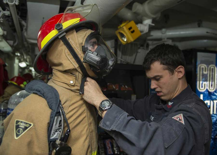 Hull Maintenance Technician 3rd Class Cino Domenique, left, has his firefighting ensemble checked by Damage Controlman 1st Class Shawn Dreyer during a mobility damage control certification evaluation by Afloat Training Group Western Pacific aboard the Arleigh Burke-class guided-missile destroyer USS Stethem (DDG 63). The test evaluates a crew on their damage control readiness to maintain a deployable status. (U.S. Navy photo by Mass Communication Specialist 3rd Class Gregory A. Harden II/Released)