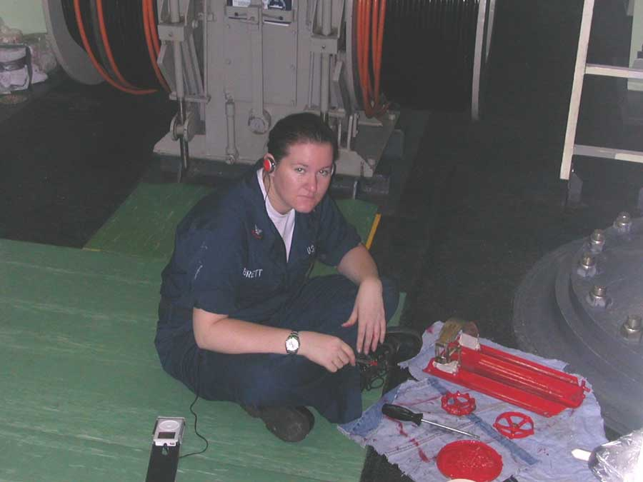 Jeni Brett paints handwheels in a sonar equipment space while on deployment in 2005. Photo courtesy of the author.