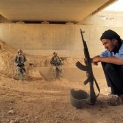 An Iraqi man out on patrol with U.S. soldiers takes a break beneath a bridge. Photo by Nathan S. Webster.