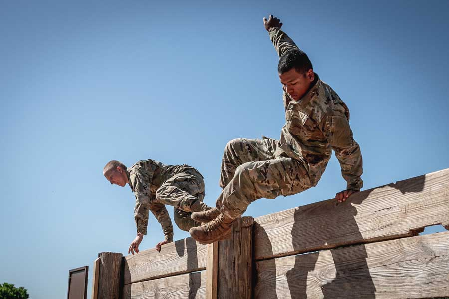 Basic trainees at Fort Sill, Oklahoma, jump over a wall during an obstacle course training in April. Photo by Sgt. Amanda Hunt, courtesy of U.S. Army.