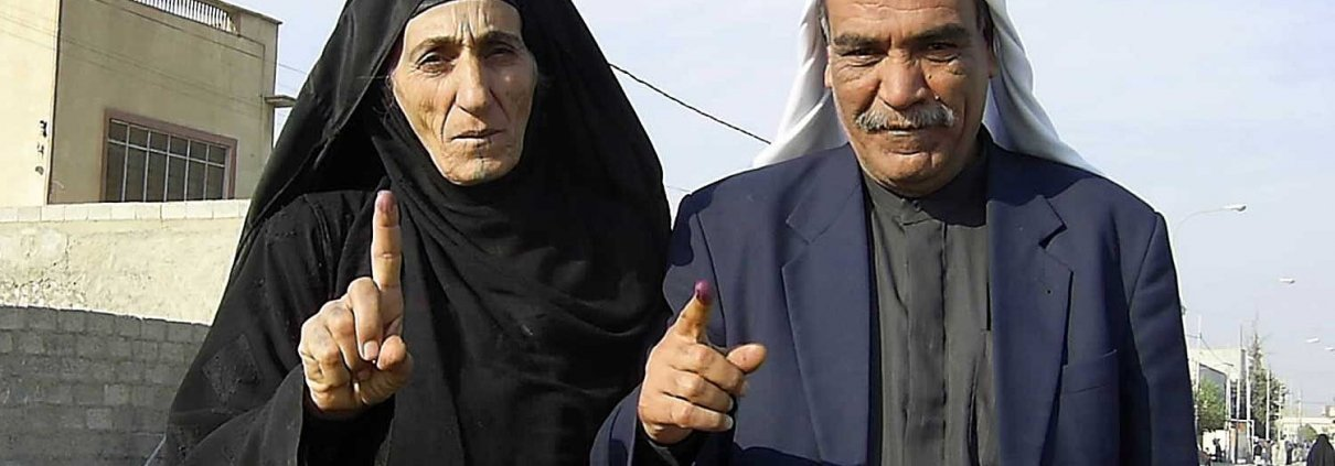 Two voters in Kirkuk in Iraq's first election of a democratic government since the fall of Saddam Hussein in 2003 display their ink-stained fingers in 2005. Photo courtesy of the Defense Department.