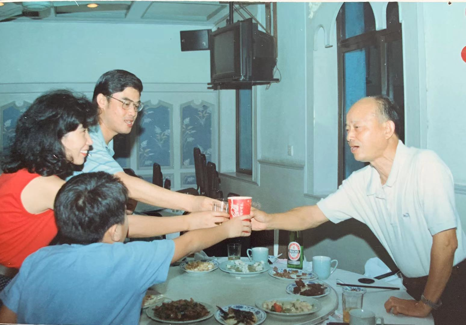 Hunter Lu, back toward camera, shares a toast with his mother, father, and grandfather. Photo courtesy of the author.