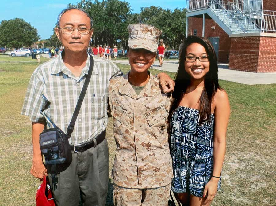 Ohu (center) stands with her father Ahr Yu (left) and sister Pan Phyu after she earns the title of Marine. Courtesy of Pan Phyu.