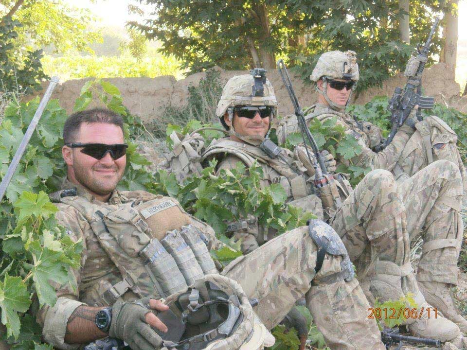 Mike McGuinness, left, sits in a row of grapevines in Afghanistan with Keith Ayres and Justin Rose.
