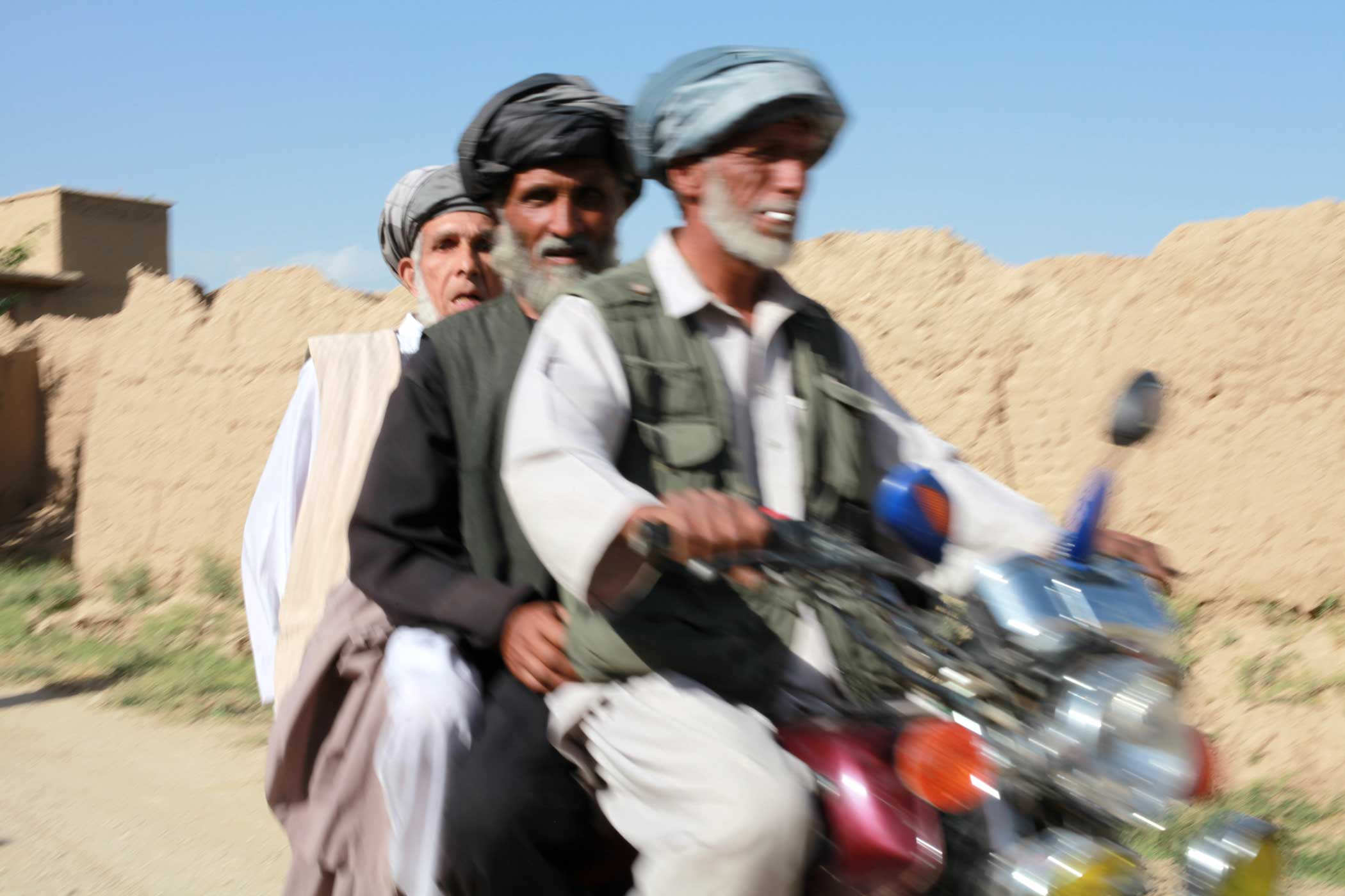 Three Afghan men share a motorcycle in Bagram, Afghanistan, in 2009. Photo by Staff Sgt. Teddy Wade, courtesy of U.S. Army.