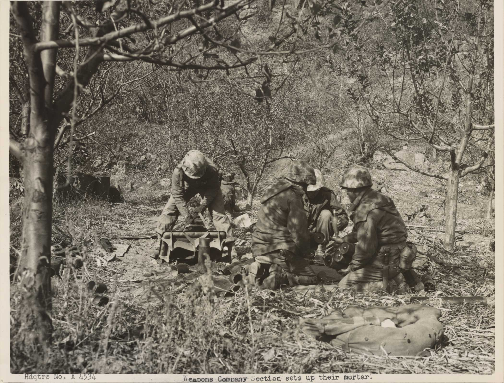 A Marine Corps weapons company section sets up their mortar to take communist positions under fire near Chosin Reservoir. Photo by Katie Lange, courtesy of the U.S. Marine Corps.