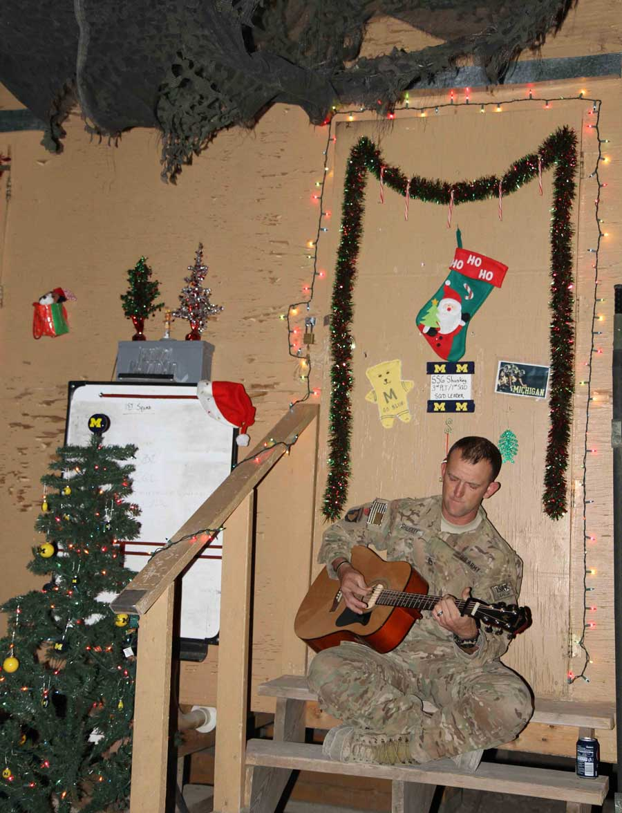 """Staff Sgt. Jonathon Shuskey, an infantry squad leader, assigned to Company D, 3rd Battalion, 187th Infantry Regiment, 3rd Brigade Combat Team """"Rakkasans,"""" 101st Airborne Division (Air Assault), plays a guitar on the steps of his room at Combat Outpost Tera Zeyi, on Christmas night in 2012. Photo by Sgt. 1st Class Abram Pinnington, courtesy of U.S. Army."""