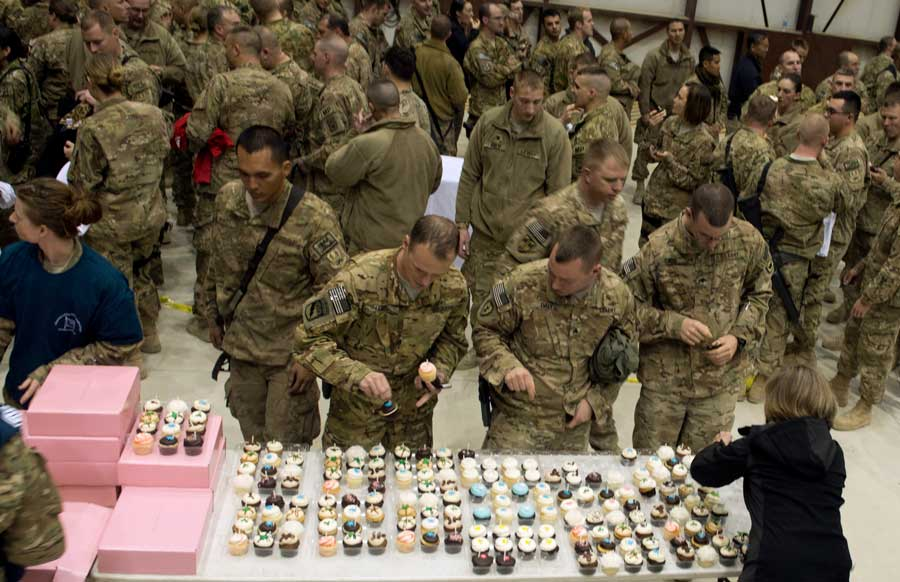 Chairman of the Joint Chiefs of Staff's wife Deanie Dempsey gives out donated cupcakes to soldiers after a USO show in Bagram, Afghanistan, in 2013. Photo by D. Myles Cullen, courtesy of the Defense Department.