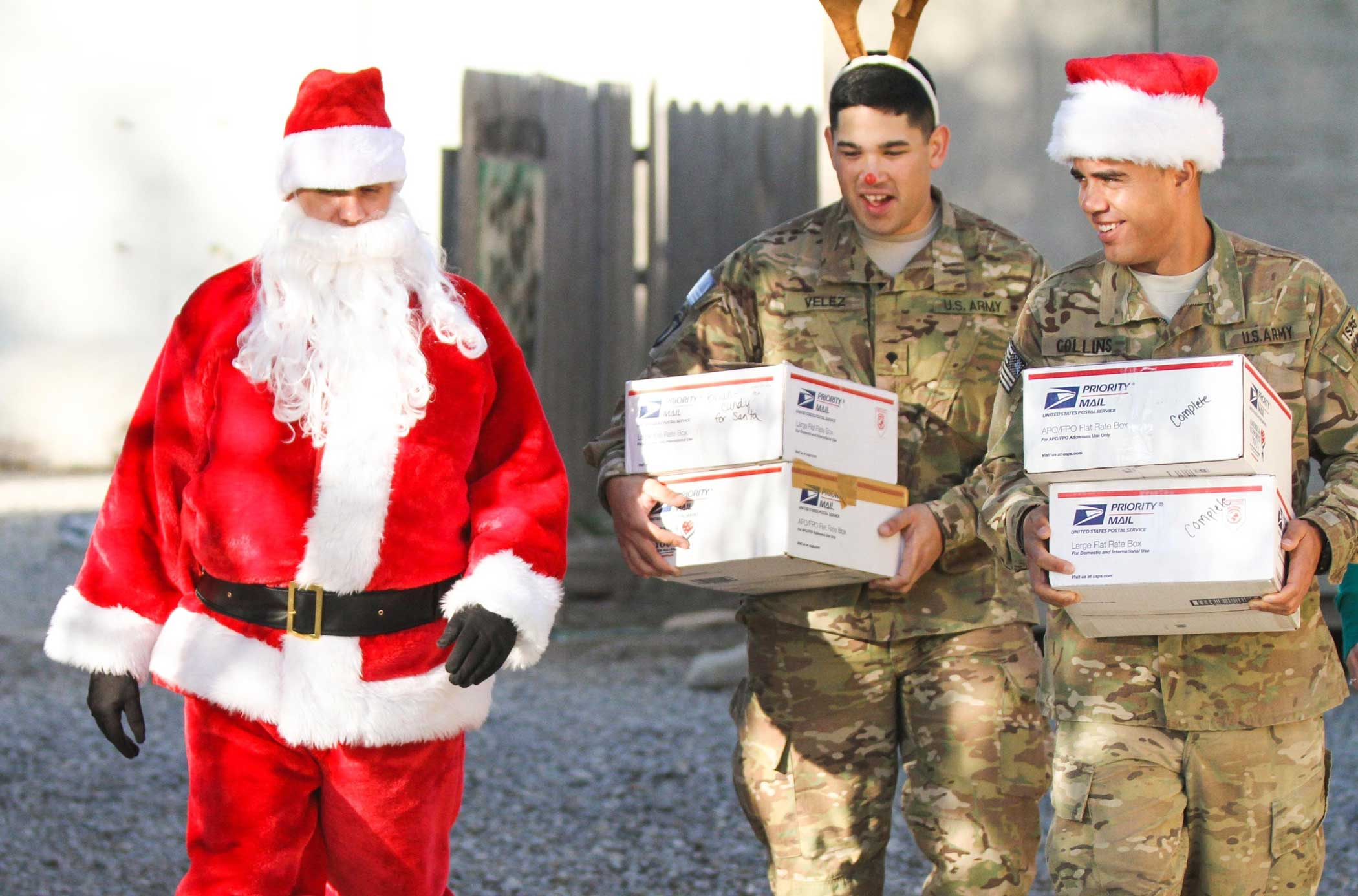 """Chief Warrant Officer 2 Brian Boase, an intelligence chief, Headquarters, Headquarters Company, 3rd Brigade Combat Team """"Rakkasans,"""" 101st Airborne Division (Air Assault), walks with two soldiers dressed as """"Santa's Helpers"""" while they deliver care packages at Forward Operating Base Salerno, Afghanistan, Dec. 25, 2012. Photo by Spc. Brian Smith-Dutton, courtesy of U.S. Army."""