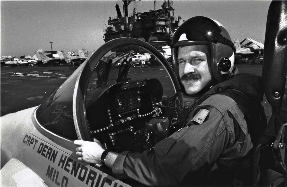 Mark Fox poses in a Hornet with the USS Saratoga in the background a few days after his battle with an Iraqi MiG. Photo courtesy of Fox.