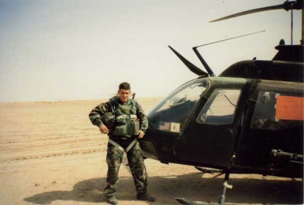 Fred Wellman stands next to his Kiowa OH-58C, The Mad Penguin, in Iraq. Photo courtesy of Wellman.