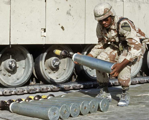 An ammunition specialist carries a 105 mm armor-piercing, discarding sabot round, to be used in an M1 Abrams tank, during Desert Shield. Photo by Sgt. Brain Cumper, courtesy of U.S. Army.