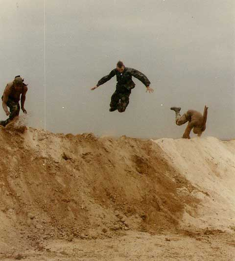Three soldiers with the 17th Signal Battalion celebrate the end of the ground war by performing backflips off sand berms.