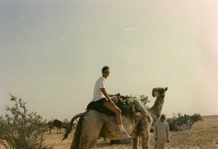 Kelly Kennedy rides a camel after running into a herd of them somewhere in the desert after Desert Storm ended.