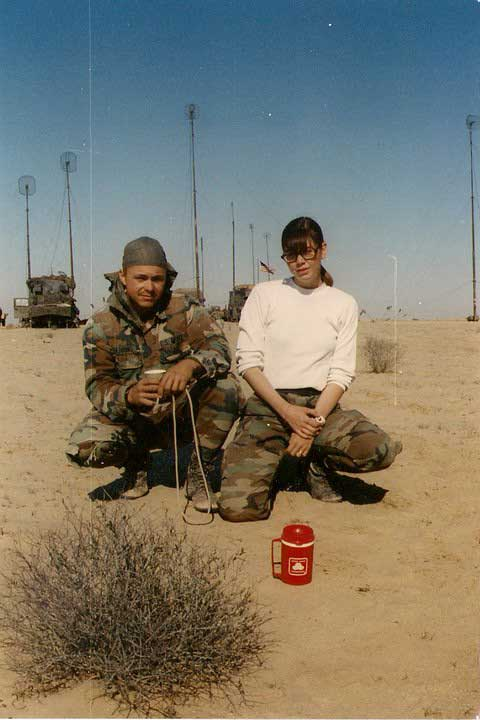 Spc. Dwayne Herring and PFC Kelly Kennedy pose in front of a communications node center somewhere in the Persian Gulf.