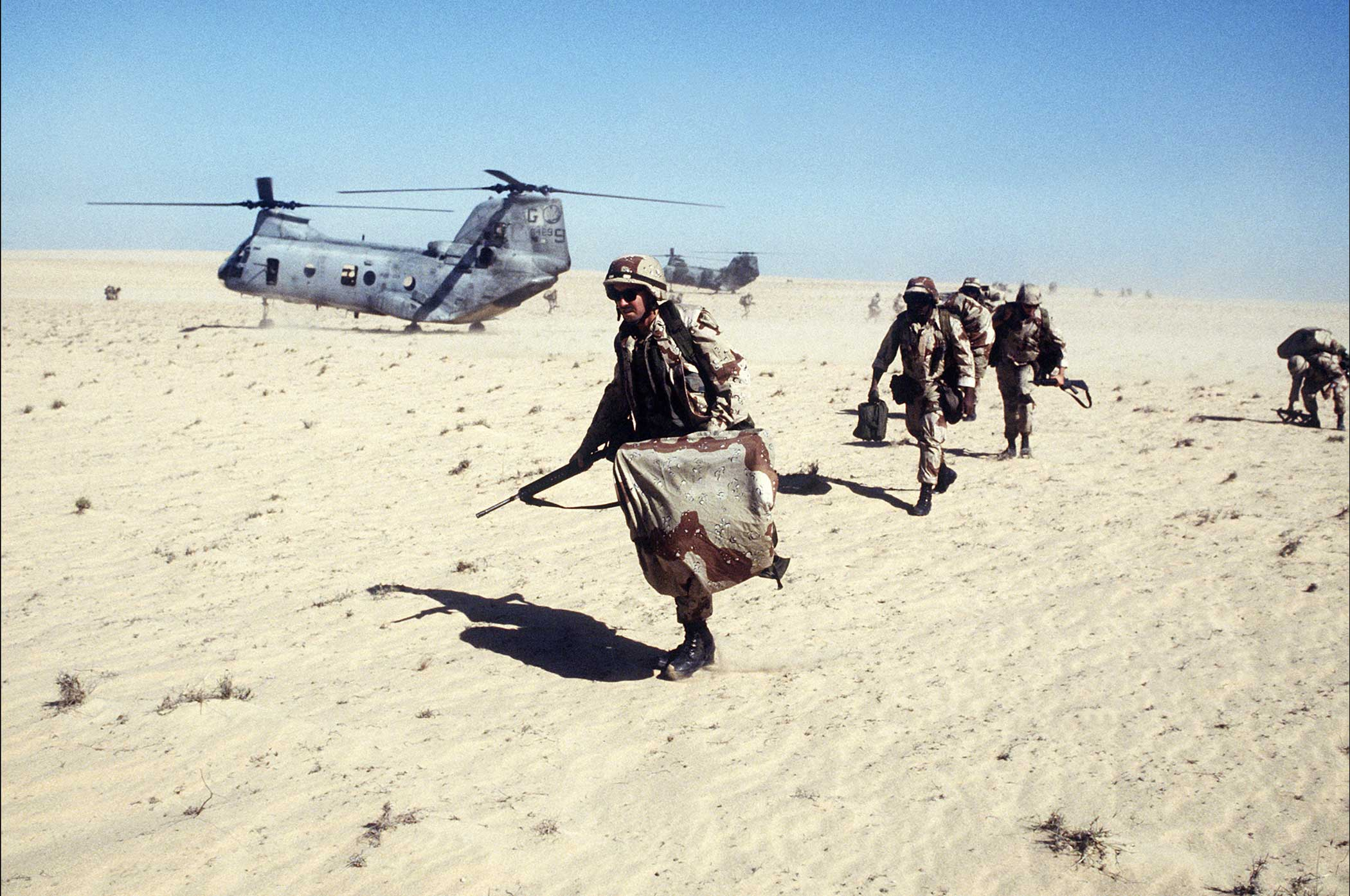 U.S. Marines assigned to the 2nd Marine Division's Charlie Company, 1st Battalion, move out on a mission after disembarking from a CH-46E Sea Knight helicopter during Exercise Imminent Thunder, part of Operation Desert Shield. Photo by Tech. Sgt. H.H. Deffner, courtesy of U.S. Air Force.
