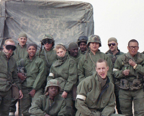 Soldiers, including the author (far right back row), from the 17th Signal Battalion pose in MOPP gear during the ground war.