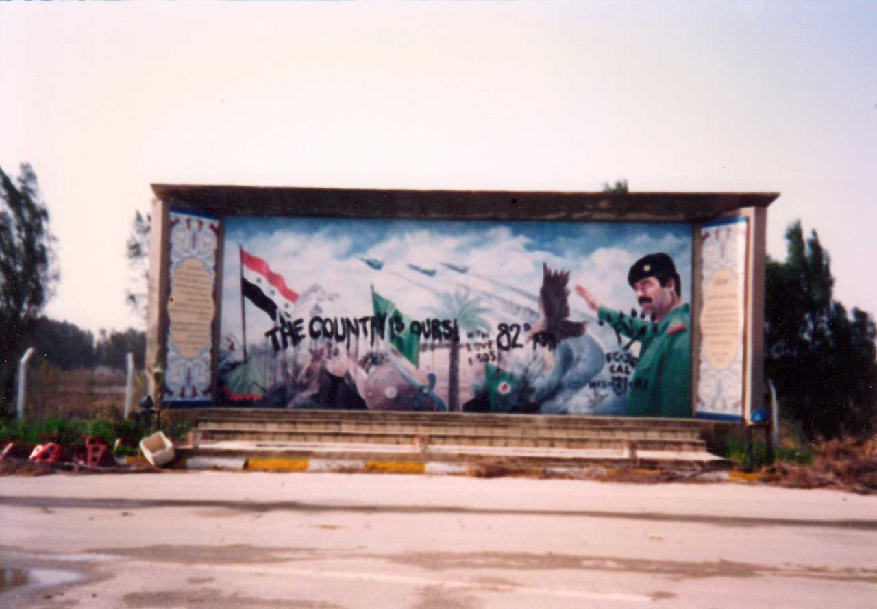 """The Country Is Ours,"" signed ""82nd."" The work of two soldiers serving in the 82nd Airborne, the defaced mural of Saddam Hussein was located near the front gate of Tallil Air Base. Photo courtesy of Harry L. Whitlock."