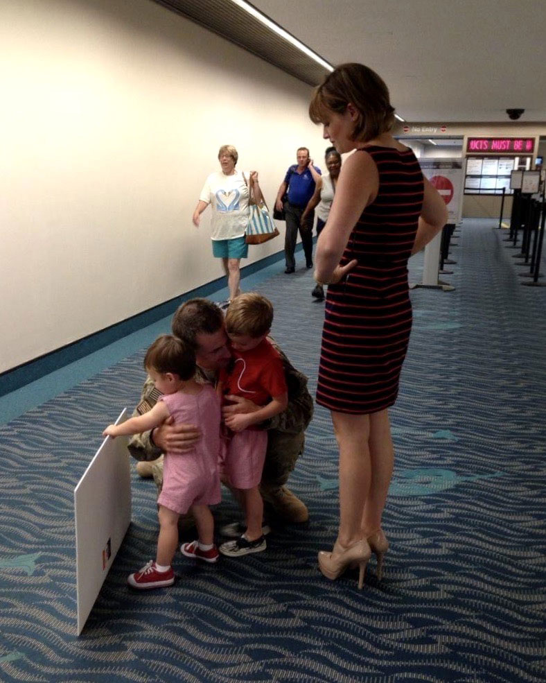 Jenny Lynne Stroup and her children greet Matthew Stroup in an airport terminal after a nine-month deployment in 2013. Photo courtesy of the author.