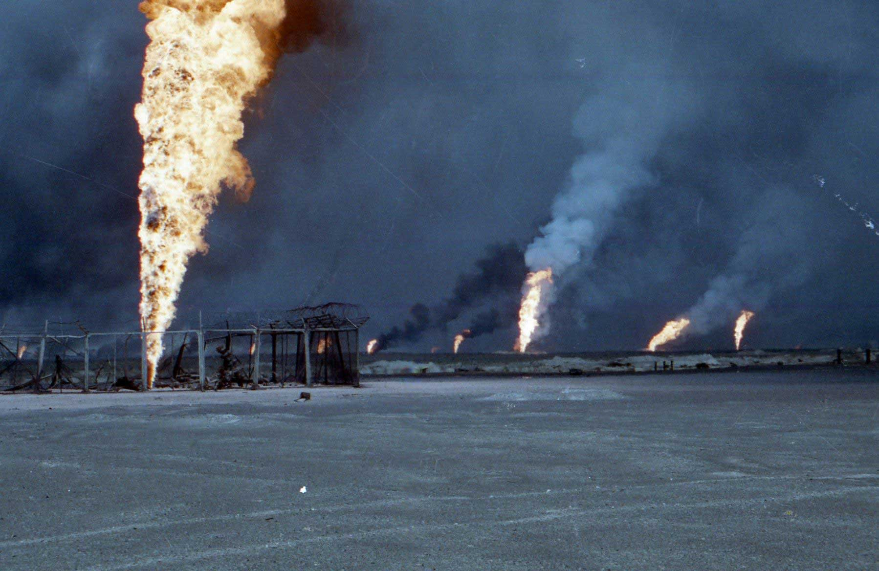 Oil wells in Kuwait fill the midday sky with smoke. Iraqi President Saddam Hussein's troops lit 650 wells on fire as they retreated, causing a crisis as Kuwait worked for nine months to put them out.