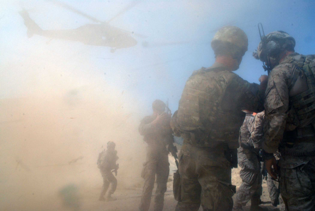 Coalition special operations forces members brace against the rotor-wash of an inbound U.S. Army UH-60 Black Hawk helicopter near the village of Bagh, Arghandab district, in 2012. Photo by Petty Officer 3rd Class James Ginther, courtesy of U.S. Navy.