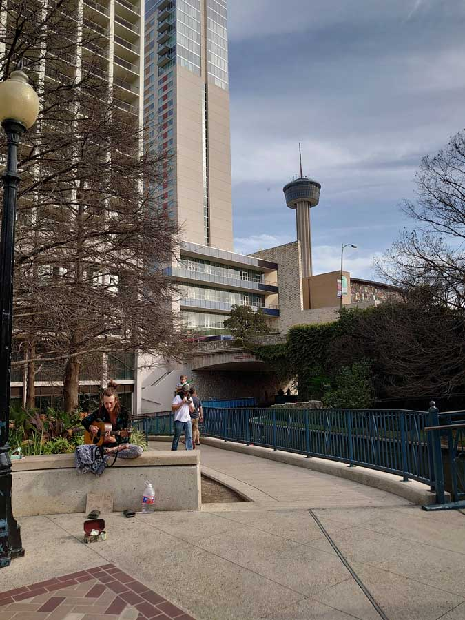 "A busker plays John Lennon's ""Imagine"" on the San Antonio River Walk in February of 2020. Photo courtesy of the author."