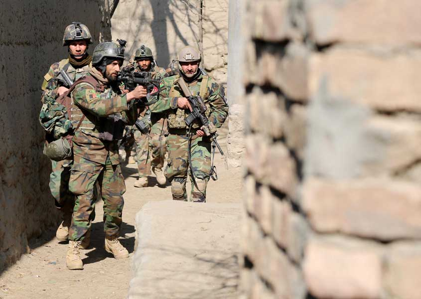 Afghan National Army commandos with the 6th Special Operations Kandak patrol an alley in Tagab District, Afghanistan, in February 2013. Photo by Pfc. James K. McCann, courtesy of U.S. Army.