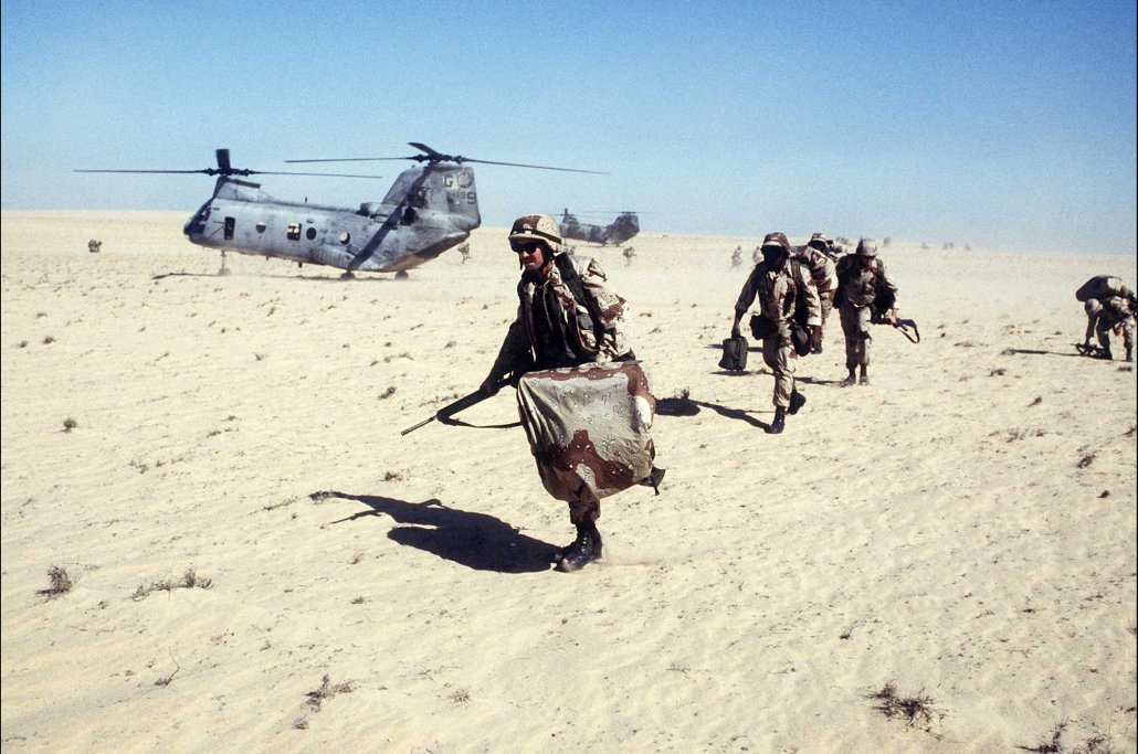 U.S. Marines assigned to the 2nd Marine Division's Charlie Company, 1st Battalion, move out on a mission after disembarking from a CH-46E Sea Knight helicopter during Exercise Imminent Thunder, part of Operation Desert Shield. Photo by Tech. Sgt. H. H. Deffner, courtesy of U.S. Air Force.