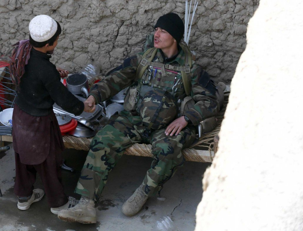 An Afghan National Army commando with the 6th Special Operations Kandak greets a child in Tagab District, Afghanistan, in February 2013. Photo by Pfc. James K. McCann, courtesy of U.S. Army.
