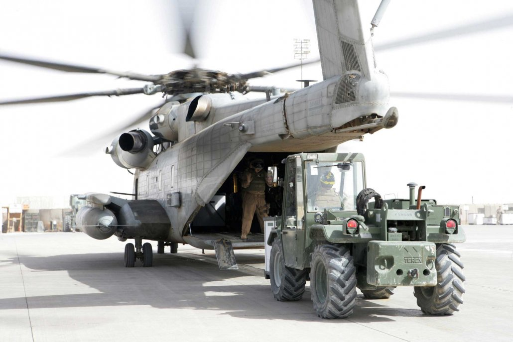A Marine helps guide a forklift as it loads cargo onto a CH-53E Super Stallion helicopter provided by Marine Heavy Helicopter Squadron 361 on the flight line of Al Asad Air Base, Iraq, in 2008. Photo by Sgt. Rome M. Lazarus, courtesy of U.S. Marine Corps.