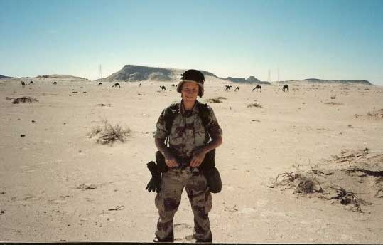Anthony Hardie stands in front of a group of camels during Operation Desert Storm. Photo courtesy of Anthony Hardie.