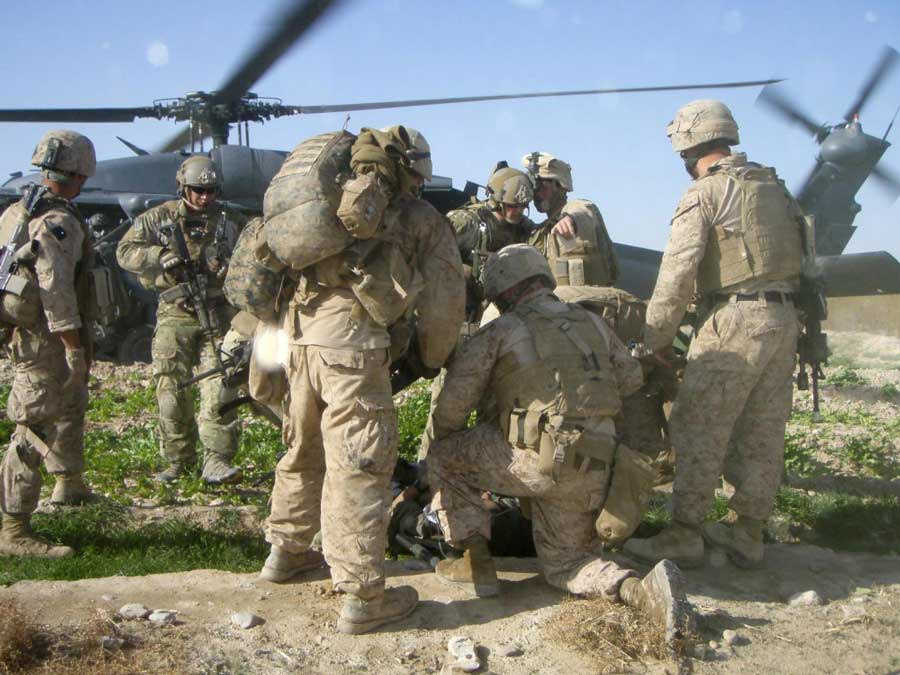 U.S. Marines and corpsmen with 3rd Battalion, 8th Marines medically evacuate an Afghan civilian brought to 3rd Platoon's patrol base in Kakar village in March 2011. The local farmer was injured by an improvised explosive device. Photo by Lance Cpl. Kevin Hassett, courtesy of U.S. Marine Corps.