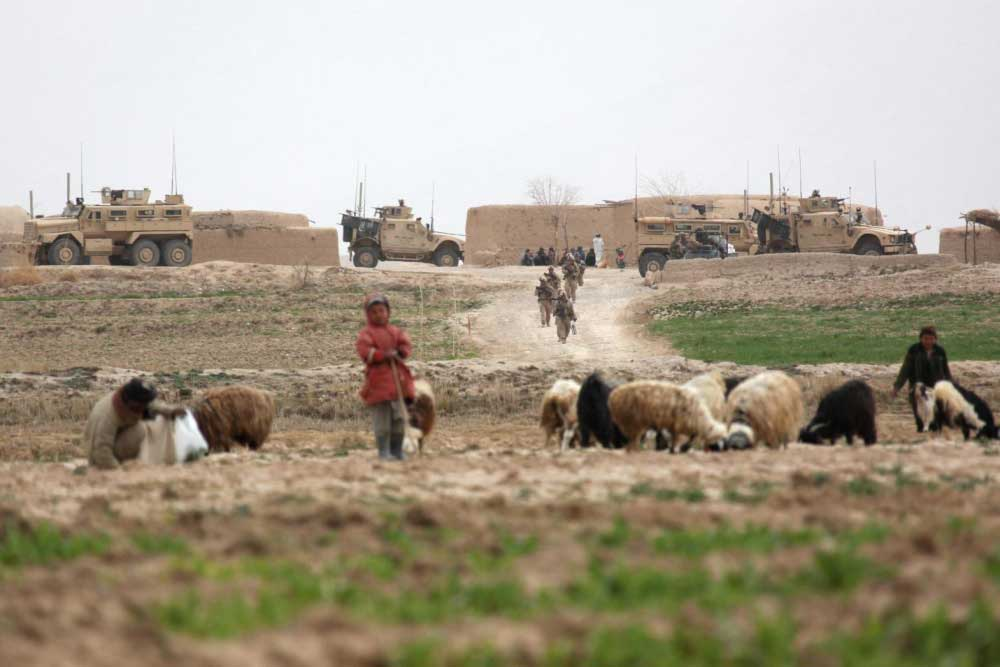 U.S. Marines with 3 Battalion, 8th Marines begin a patrol from Kakar village, Helmand province, Afghanistan in February 2011. Photo by Gunnery Sgt. Bryce Piper, courtesy U.S. Marine Corps.