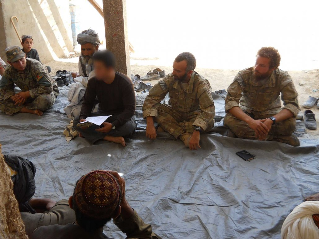 The author, far right, and a Special Operations soldier listen to Afghan leaders at a shura. Photo courtesy of the author.
