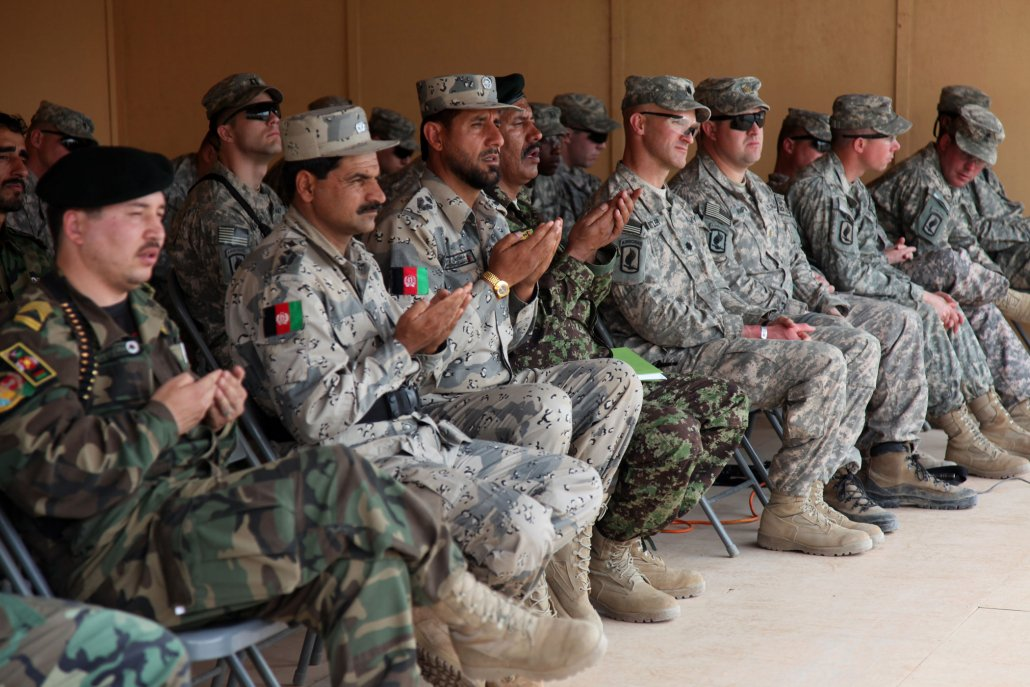 U.S. Army Lt. Col. William J. Butler, commander, 2/503 IN (Airborne), and Lt. Col. Sher Mohammad, commander, 6th Kandak, Afghan National Army, and their staff during an assumption of command ceremony for Lt. Col. Sher Mohammad at Forward Operating Base Joyce, Konar province, Afghanistan, in 2010. Photo by Sgt. Corey Idleburg, courtesy of U.S. Army.