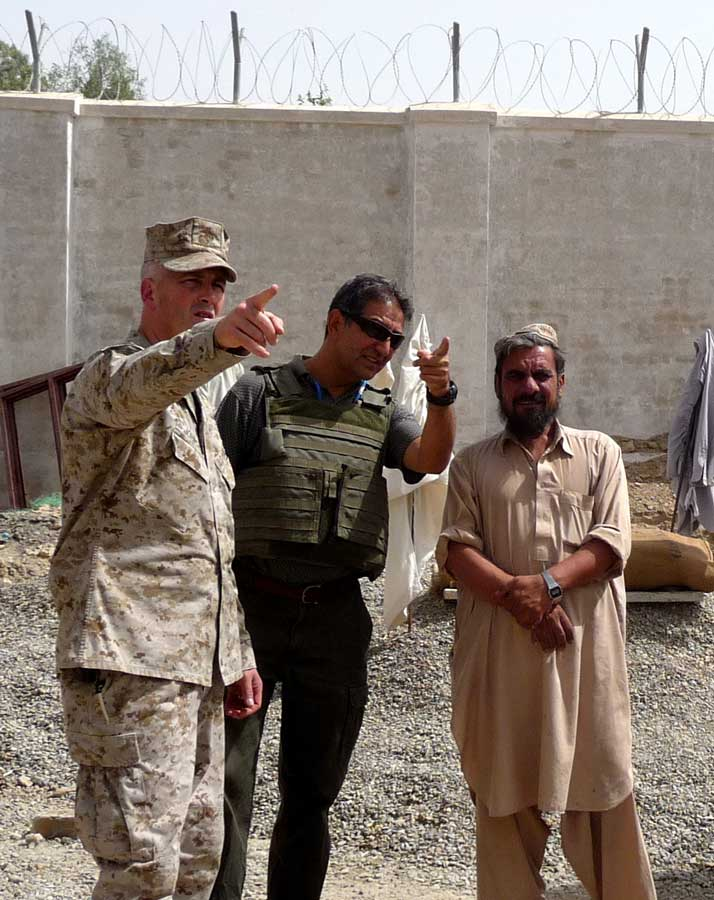Atiqualla Rahin, U.S. Marine Chief Warrant Officer Bruce Johnson, and an Afghan contractor walk around the grounds of a new building site for a men's detention facility in Lashkar Gah, Afghanistan, in 2010. Photo by Lt. j.g. Jennifer Franco. Courtesy of U.S. Marine Corps.